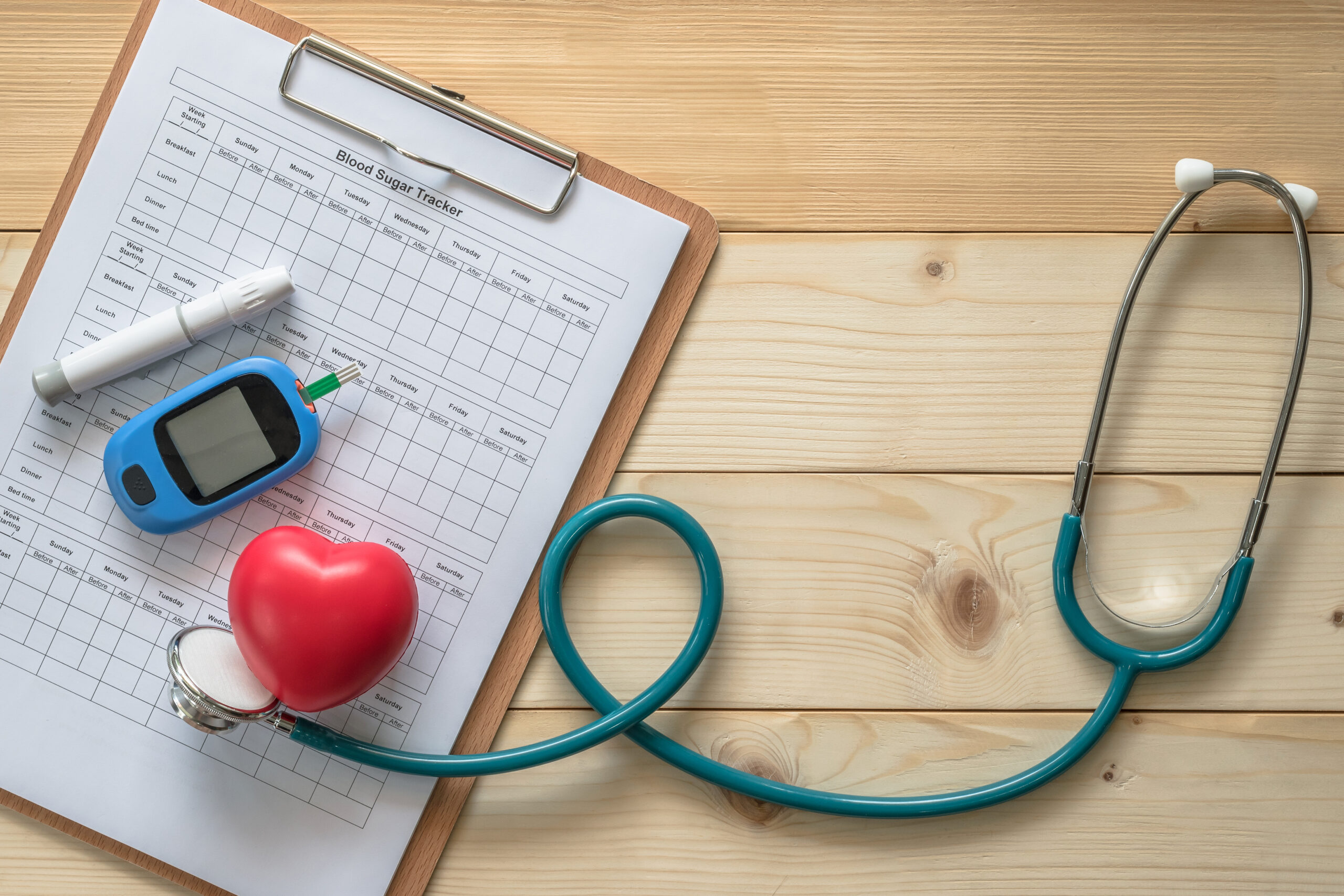 Stethoscope with diabetes blood tester on clipboard with heart
